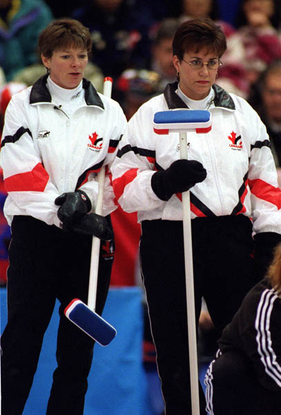Canada's Jan Betker (L) and Sandra Schmirler watch as their opponents take their turn during a curling match at the 1998 Nagano Winter Olympics. (CP PHOTO/COA)
