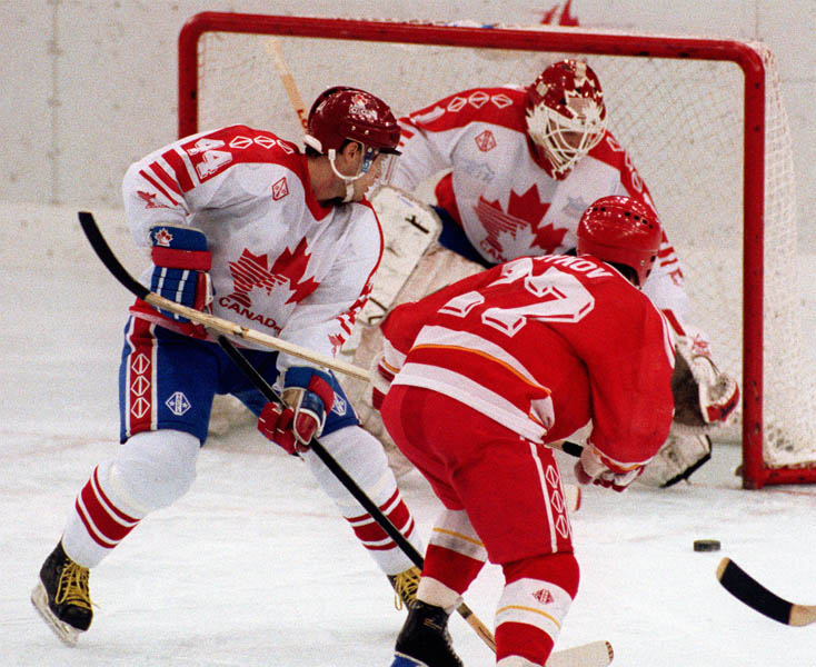 Canada's Curt Giles (left) and Sean Burke (goalie) competing in the Gold Medal game against the Unified Team in which Canada won Silver at the 1992 Albertville Olympic winter Games. (CP PHOTO/COA/Scott Grant)