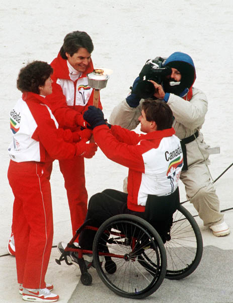 Canada's Cathy Preistner (left) and Ken Read (centre) receive the olympic flame from Rick Hanson during the opening ceremonies of the 1988 Winter Olympics in Calgary. (CP PHOTO/COA/ T. O'lett)