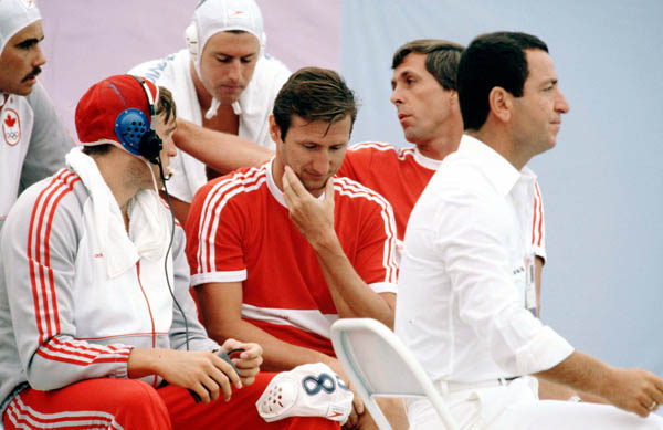 Canada's coach for the men's waterpolo team Gabor Csepregi (centre) listens to a player at the 1984 Olympic Games Los Angeles. (CP Photo/COA/Tim O'lett)