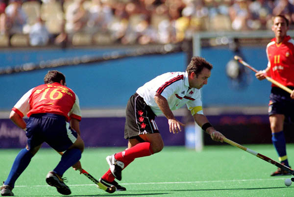 Canada's Peter Milkovich (white) participates in field hockey action at the 2000 Sydney Olympic Games. (CP Photo/ COA)