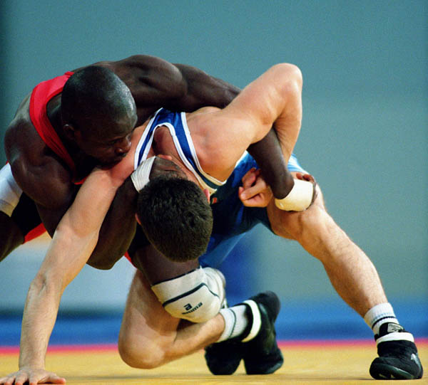 Canada's Daniel Igali (red) competes in the wrestling event at the 2000 Sydney Olympic Games. (CP Photo/ COA)