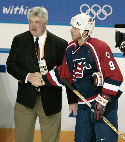 Canada's men's team coach Pat Quinn is congratualated by Mike Modano of the U.S.  after Canada defeated the U.S. 5 - 2 to take the gold medal at the Winter Olympics in West Valley City, Utah, Sun., Feb. 24, 2002 . (CP PHOTO/COA/Mike Ridewood)