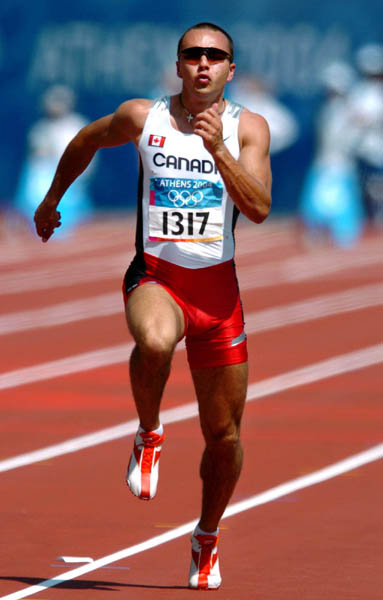 Canadian sprinter Nicolas Macrozonaris of Laval, Quebec, runs during the 100m heat during the Athens 2004 Summer Olympic Games Saturday, August 21, 2004. Macrozonaris crossed the line with a time of 10.40 to move on. (CP PHOTO/COCAndre Forget)