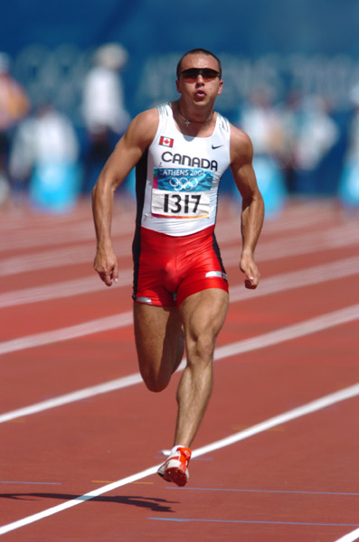 Canadian sprinter Nicolas Macrozonaris of Laval, Quebec, runs during the 100m heat during the Athens 2004 Summer Olympic Games Saturday, August 21, 2004. Macrozonaris crossed the line with a time of 10.40 to move on. (CP PHOTO/COC-Andre Forget)