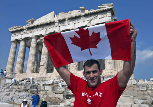 Judo athlete Nicolas Gill of Montreal poses with the Canadian flag in front of the Parthenon in Athens, Thursday, August 10, 2004. Gill will carry the flag to lead the Canadian team at the opening ceremonies of the Olympics on Friday. (CP PHOTO/COC-Mike Ridewood)