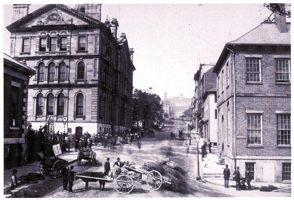 Photo en noir et blanc d'une rue d'Halifax, en 1899. Au premier plan, on voit deux chariots sur lesquels se trouvent différents produits; un des deux chariots est tiré par un bœuf. On aperçoit aussi d'autres vendeurs et des piétons du côté gauche de la rue, qui se prolonge au loin.