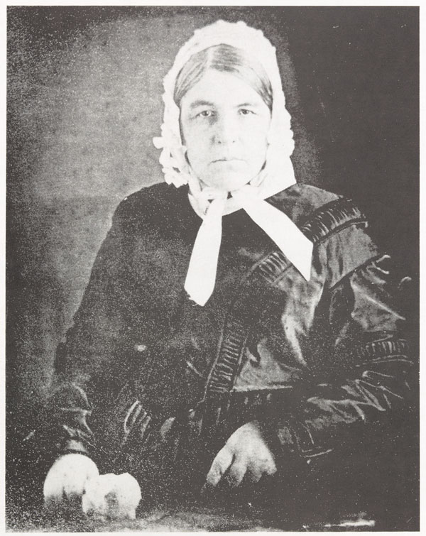 Black-and-white photograph of a seated elderly lady in a black dress and white cap tied beneath her chin. She is looking straight at the camera.