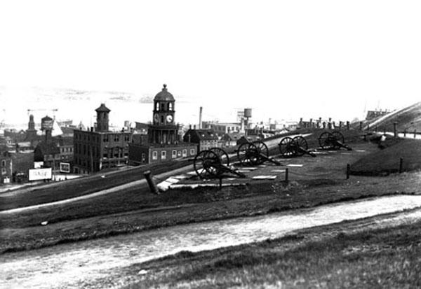 Photo en noir et blanc prise à partir d'une colline. On aperçoit des canons au premier plan, et au loin, la tour de l'horloge et les édifices environnants d'Halifax.