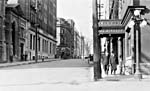 Photograph of an electric lamp post on a city street corner, 1916
