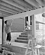 Photograph of a man and a woman painting the outside of a house with brushes