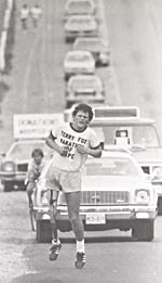 Photograph of Terry Fox, running along a roadway with a police car and a line of other cars behind him