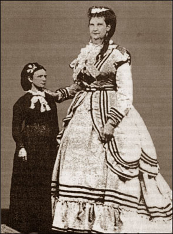 Photograph of Anna Swan, standing beside a woman of average height