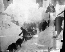 Photograph of people and dogsleds on the Chilkoot Pass summit during a snowstorm, 1898