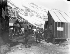 Photograph showing tarpaper shacks housing saloons, hotels and stores at the base of a mountain, 1898