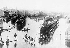 Photo montrant des gens qui se déplacent en chaloupe autour des wagons sur le terrain inondé de la gare Bonaventure, à Montréal, en 1866