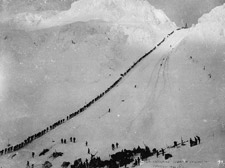 Photograph of a single line of climbers that winds all the way from the snow-covered base to the summit, Chilkoot Pass, 1898 or 1899