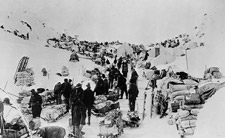 Photograph of people on a snow-covered mountain with sleds full of supplies, Chilkoot Pass, 1898
