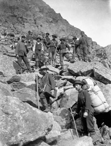 Photograph of several prospectors climbing a mountain slope in the Chilkoot Pass, circa 1897