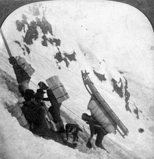 Photograph of climbers with large packs on their backs on the side of a snow-covered mountain, Chilkoot Pass, 1898