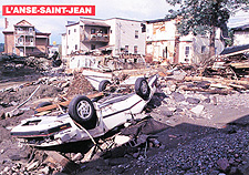 Photograph of destroyed homes and a car flipped onto its roof by the flood, 1996