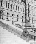 Photograph of Centre Block, with flower beds and staircase in foreground, pre-1916