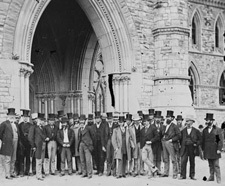 Photograph of Members of Parliament in front of entrance arch, Centre Block, May 1873