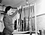 Private Nadine Manning of the Canadian Army Film and Photo Unit processing strips of censored film at Merton Park Studios. Photographer: Capt. Jack H. Smith/DND/LAC/PA-152111