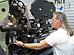 A conservator copying an original 28mm film, frame by frame, onto 35mm polyester film