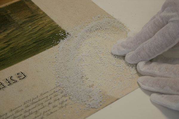 The first step was to remove as much of the surface dirt as possible. The recto of the lithograph was dry cleaned using ground white vinyl eraser: the crumbs were rolled across the surface with a light pressure to avoid pushing the dirt into the paper fibres.