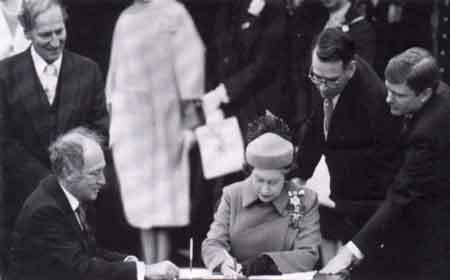 Queen Elizabeth II and Prime Minister Pierre Elliott Trudeau sign the Constitution. Ottawa, Ontario. April 17, 1982.