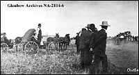 Photograph of men watching a horse race on Dominion Day in Outlook, Saskatchewan in 1909