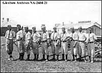 Photograph of a 10-man baseball team, wearing matching uniforms, posing for their victory photograph on July 1, 1914