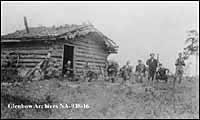 Photograph of a group of men, many playing musical instruments, gathered outside a sod-roofed log cabin in Alberta in 1911