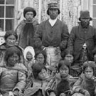 Photograph of a group of Inuit men, women and children and Reverend Peck, Pangnirtung (Pangnirtuuq), Nunavut, September 5, 1903