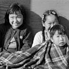 Photograph of four Inuit children sitting together on the ground, Resolute Bay (Qausuittuq), Nunavut, September 1959