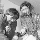 Photograph of an Inuit couple sitting in a tent. The woman is pouring water from a kettle into the man's tea cup, Eastern Arctic region, 1947