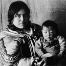 Portrait of Kookooleshook sitting on a chair in front of a canvas backdrop and holding a child on her lap, Fullerton, Nunavut, 1904