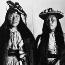 Portrait of Niviaqsarjuk (left) and Jennie (right) wearing Western style dresses and hats. This photograph was taken in a studio at Fullerton, Nunavut, 1904