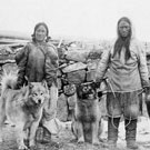 Photograph of an Inuit woman and man standing in front of stone wall with three dogs, Fullerton, Nunavut, 1904-1905