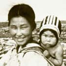 Photograph of an Inuit woman carrying an infant in a baby-pouch, unknown location, Nunavut, summer 1952