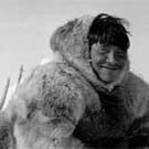 Photograph of an Inuit man, Zachery Itimangnaq, who appears to be working on his sled, at Pelly Bay (Arvilikjuaq), Nunavut, 1953
