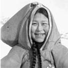 Photograph of a young Inuit woman standing in a snowy landscape, unknown location, Nunavut, no date