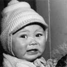 Photograph of a  young Inuit woman holding her crying infant, Iqualuit (formerly Frobisher Bay), Nunavuat, circa 1950s