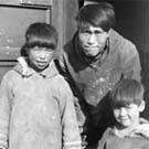 Photograph of an Inuit man and two children standing in a doorway, unknown location, (now Nunavut), unknown date