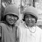 Photograph of four Inuit children standing in front of a building, Lyon Inlet, Nunavut, 1933