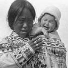 Photograph of an Inuit woman carrying a crying child, unknown location, Nunavut, circa 1926-1943