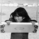 Photograph of an Inuit girl playing on a swing, Chesterfield Inlet (Igluligaarjuk), Nunavut, September 5, 1958