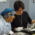 Photo de l'aîné Abraham Ulayuruluk et Joanna Quassa regardant un album photos d'Inuits dans les collections de Bibliothèque et Archives Canada, Ottawa, octobre 2005