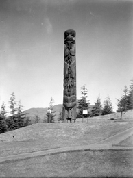 Black and white photograph of a single totem pole on a gentle hill surrounded by well trimmed grass, with a woman standing next to it, looking up